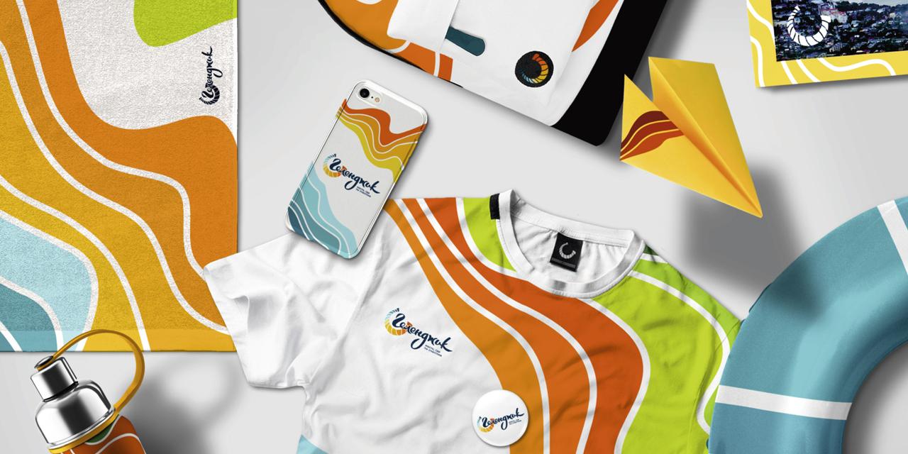 Айдентика туристического бренда Геленджика в сувенирной продукции: пляжное полотенце, бутылка для воды, футболка, чехол для телефона, рамка для фотографий